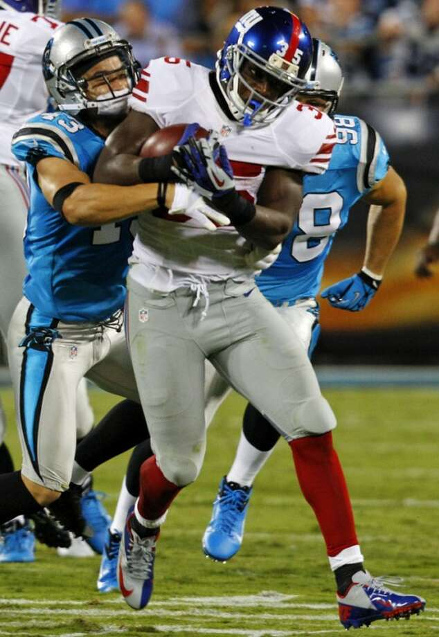 New York Giants running back Andre Brown (35) rushes as Carolina Panthers cornerback Josh Norman (24) defends during the first quarter of an NFL football game in Charlotte, N.C., Thursday, Sept. 20, 2012. (AP Photo/Chuck Burton)