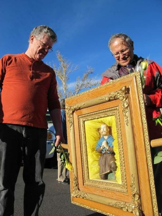 This April 19, 2013 photo shows Our Lady of Sorrows Catholic Church parishioners Nick McGovernor, left, and Orlando Lucero talking about the framed statue of San Ysidro, the patron saint of farmers, after a prayer procession for rain in Bernalillo, N.M. From the heart of New Mexico to West Texas and Oklahoma, the pressures of drought have resulted in a resurgence of faith, from Christian preachers and Catholic priests encouraging prayer processions to American Indian tribes using their closely guarded traditions in an effort to coax Mother Nature to deliver some much needed rain. (AP Photo/Susan Montoya Bryan)
