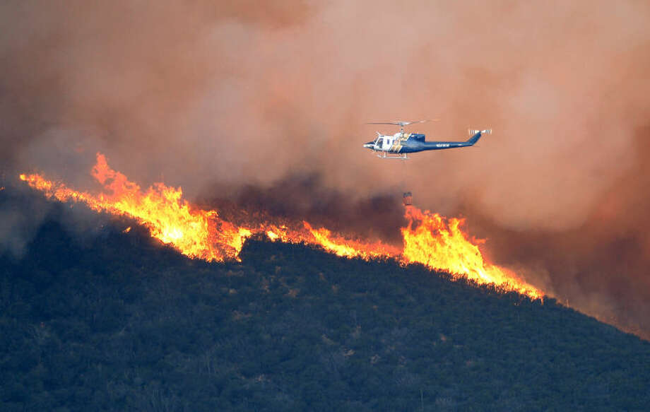 A water dropping helicopter gets ready to make a drop on a fire burring in Point Mugu State Park during a wildfire that burned several thousand acres, Thursday, May 2, 2013, in Ventura County, Calif. (AP Photo/Mark J. Terrill)
