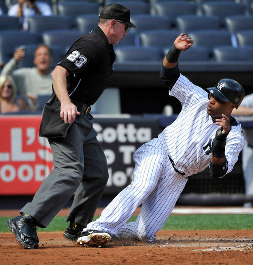 New York Yankees' Robinson Cano, right, almost slides into home plate umpire Lance Barksdale, left, as he scores on a sacrifice fly by Curtis Granderson during the first inning of the first baseball game of a day-night doubleheader against the Toronto Blue Jays Wednesday, Sept. 19, 2012, at Yankee Stadium in New York. (AP Photo/Bill Kostroun) / FR51951 AP