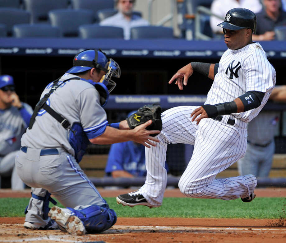 New York Yankees' Robinson Cano, right, scores on a sacrifice fly by Curtis Granderson as Toronto Blue Jays catcher Jeff Mathis fields the throw during the first inning of the first baseball game of a doubleheader, Wednesday, Sept. 19, 2012, at Yankee Stadium in New York. (AP Photo/Bill Kostroun) / FR51951 AP