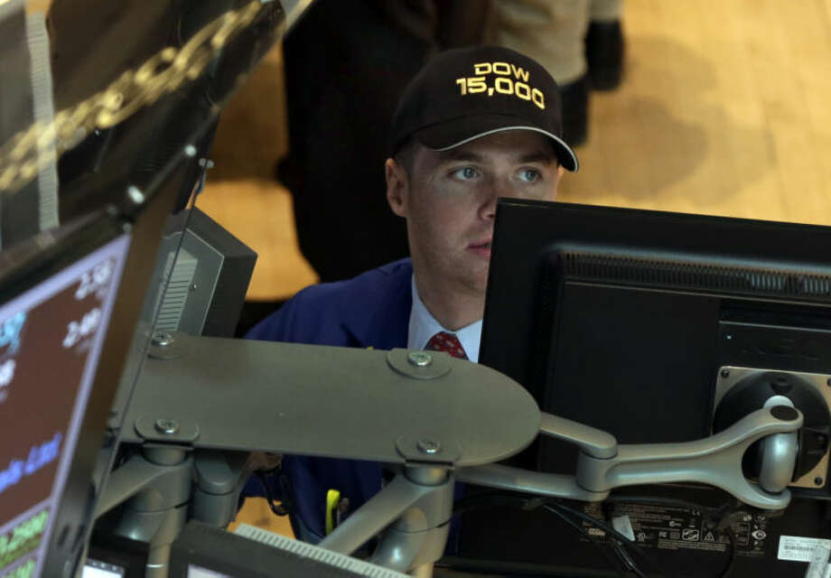 """Specialist Frank Masiello wears a """"Dow 15,000"""" hat as he works at his post on the floor of the New York Stock Exchange Friday, May 3, 2013. A big gain in the job market is lifting the stock market to a record high. The Dow Jones industrial average crossed 15,000 for the first time, and the Standard and Poor's 500 index, a broader market measure, rose above 1,600.(AP Photo/Richard Drew)"""
