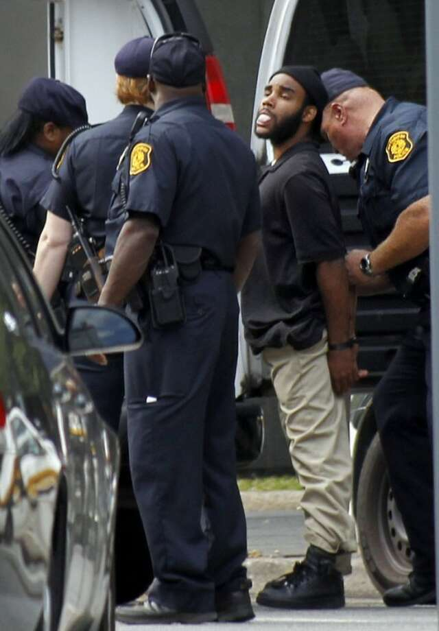 Pittsburgh police take Klein Michael Thaxton into custody after he held a businessman hostage at gunpoint inside a downtown Pittsburgh office building for more than five hours Friday, Sept. 21, 2012. Thaxton, 22, posted Facebook updates during the standoff, then surrendered to authorities without incident, police said. The man he took hostage was unhurt. (AP Photo/Keith Srakocic)