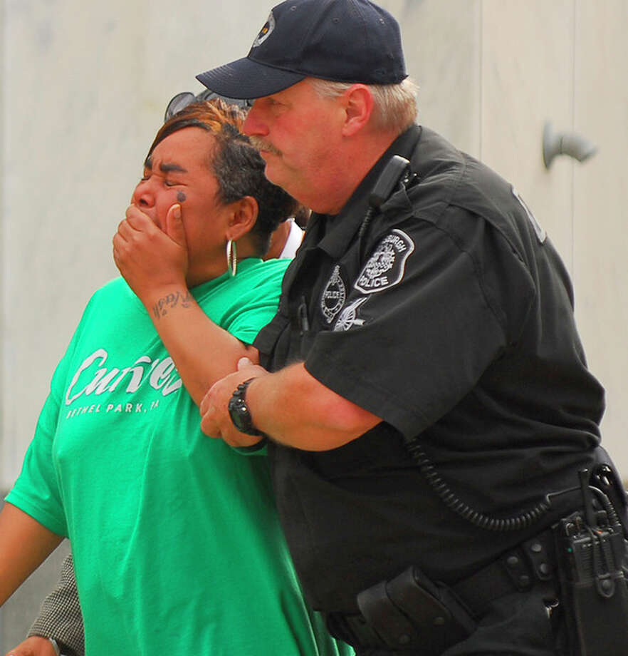 Ronda Thaxton, the mother of Klein Michael Thaxton is escorted by Pittsburgh Police Officer Ray Kain to the command center during the standoff atThree Gateway Center, Friday, Sept. 21, 2012. Klein Michael Thaxton, 22, held a businessman hostage inside the office building for more than five hours Friday, posting Facebook updates during the standoff, and surrendered to authorities without incident, police said. (AP Photo/The Tribune-Review, Keith Hodan) PITTSBURGH OUT / Pittsburgh Tribune-Review