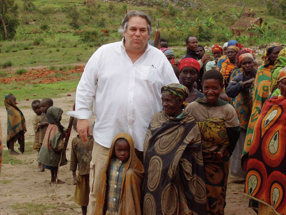 In this December 2007 photo obtained by The Associated Press, the Rev. Carl Keyes stands for a photo with impoverished people of the Batwa Tribe in Burundi during a delivery of relief supplies to the area. Keyes accompanied an established aid group to look into program possibilities, and after this trip, he created Aid for the World. (AP Photo) / Anonymous