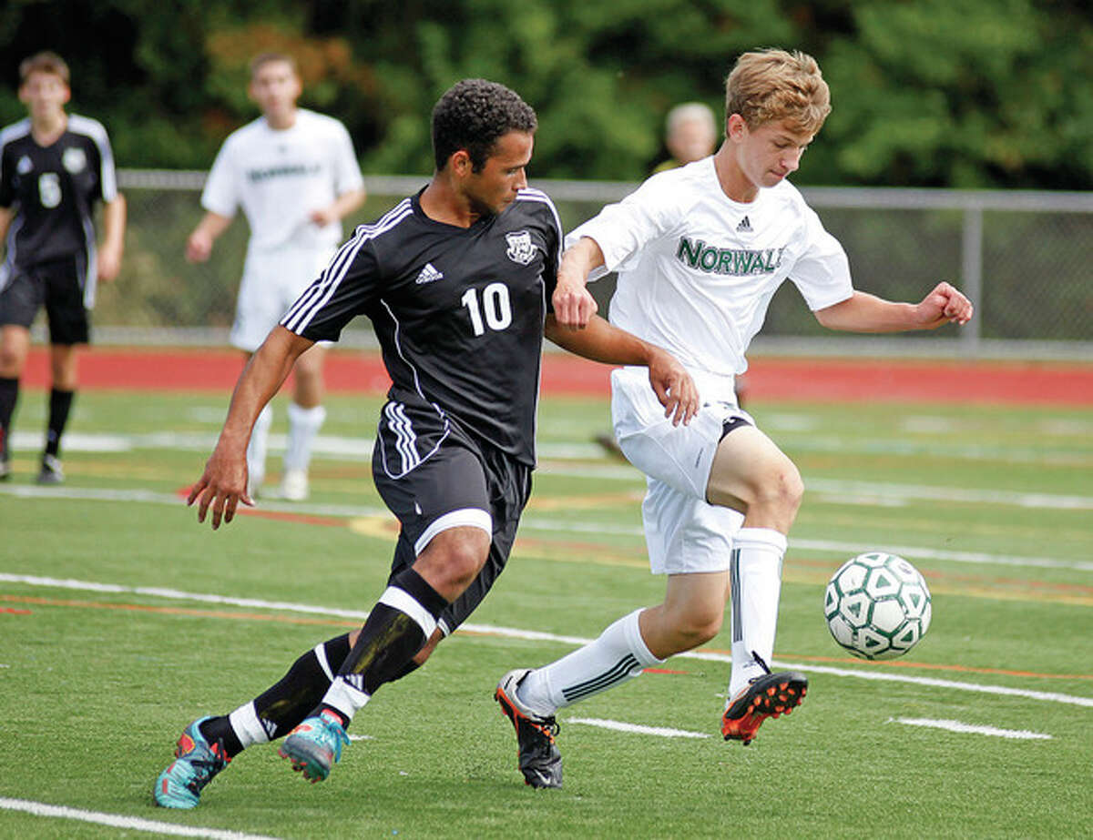 Hour photo/Danielle Robinson Norwalk's Michal Nowicki, right, plays the ball away from a Trumbull player during a home game Saturday afternoon at Testa Field in Norwalk. Norwalk shutout Trumbull by a 3-0 score.