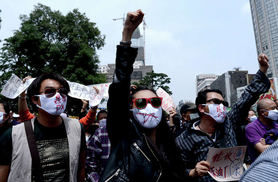 """Chinese people wear face masks with """"No to Kunming PX,"""" paraxylene, written, chant slogans as they hold protest against a planned refinery project in downtown Kunming in southwest China's Yunnan province Saturday, May 4, 2013. After word spread about an environmental protest that was planned for Saturday in the central Chinese city of Chengdu, drugstores and printing shops were ordered to report anyone making certain purchases. Microbloggers say government fliers urged people not to demonstrate, and schools were told to stay open to keep students on campus. Meanwhile, hundreds of people - many wearing mouth masks - gathered in Kunming to protest a planned refinery project in the area. The demonstrators demanded information transparency and that public health be safeguarded. (AP Photo) CHINA OUT / CHINATOPIX"""