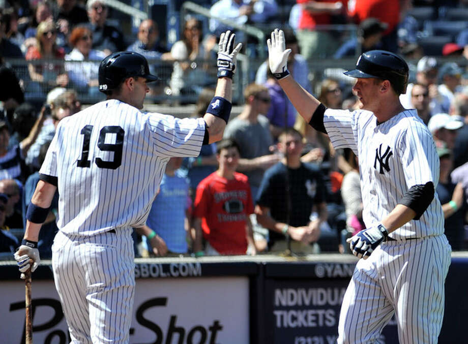 New York Yankees's Chris Stewart (19) high-fives with Lyle Overbay after Overbay hit a solo home run off of Oakland Athletics starting pitcher Bartolo Colon in the fifth inning of a baseball game at Yankee Stadium on Saturday, May 4, 2013 in New York. Stewart hit a solo home run in the third inning. (AP Photo/Kathy Kmonicek) / FR170189 AP