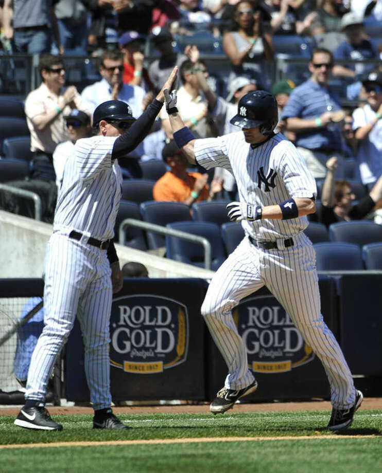 New York Yankees' Chris Stewart, right, high-fives with third base coach Rob Thomson as Stewart rounds third base after hitting a solo home run in the third inning of a baseball game against the Oakland Athletics at Yankee Stadium on Saturday, May 4, 2013 in New York. (AP Photo/Kathy Kmonicek)