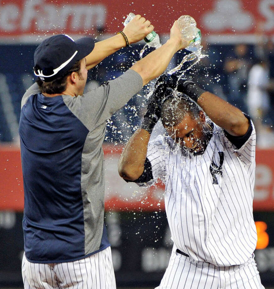 New York Yankees' Nick Swisher, left, douses teammate Eduardo Nunez with water after they defeated the Oakland Athletics 10-9 during the 14th inning of a baseball game on Saturday, Sept. 22, 2012, at Yankee Stadium in New York. (AP Photo/Bill Kostroun) / FR51951 AP