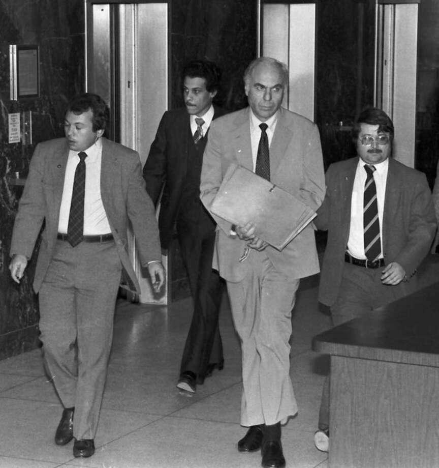 FILE - In this Jan. 22, 1983 file photo, ex-CIA agent Edwin Wilson, center, leaves federal court after a day of jury selection accompanied by U.S. Marshals in Houston. Edwin P. Wilson, a former CIA operative who was branded a traitor and convicted of shipping arms to Libya but whose conviction was later overturned after he served 22 years in prison, has died, Sept. 10, 2012. He was 84. (AP Photo/File) / AP