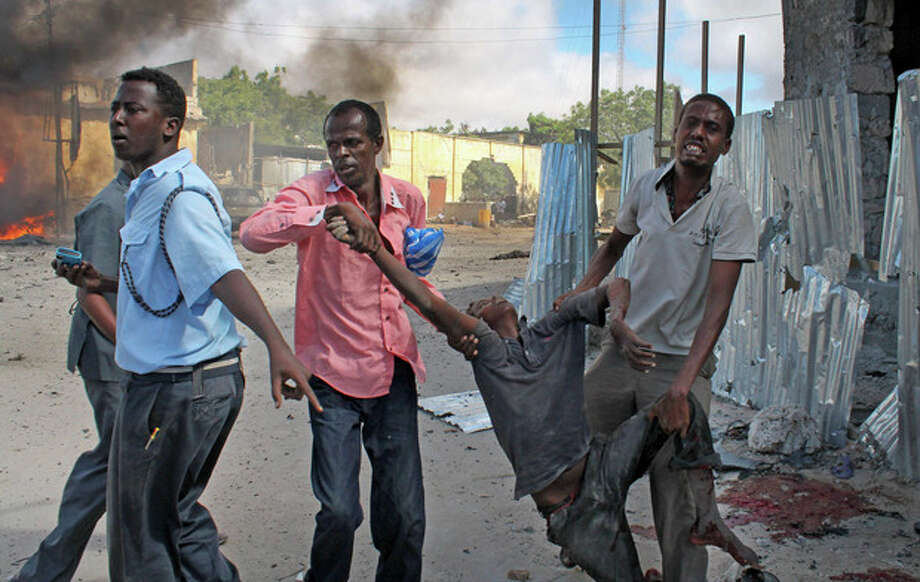 Somali men carry away a wounded civilian following a suicide car bomb blast in the capital Mogadishu, Somalia Sunday, May 5, 2013. A Somali police official at the scene said four civilians and a soldier were killed after the suicide bomber attempted to ram a car laden with explosives into a military convoy. (AP Photo/Farah Abdi Warsameh) / AP