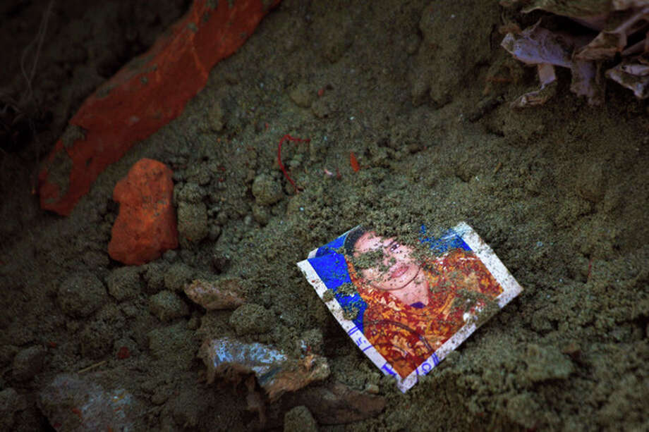 "A photo of a missing garment worker is partially buried in soil at the site of the garment factory building collapse in Savar, near Dhaka, Bangladesh, Saturday, May 5, 2013. The death toll in the accident rose to more than 530 on Saturday, a day after the country's finance minister downplayed the impact of the disaster on the garment industry, saying he didn't think it was ""really serious."" (AP Photo/Ismail Ferdous) / AP"
