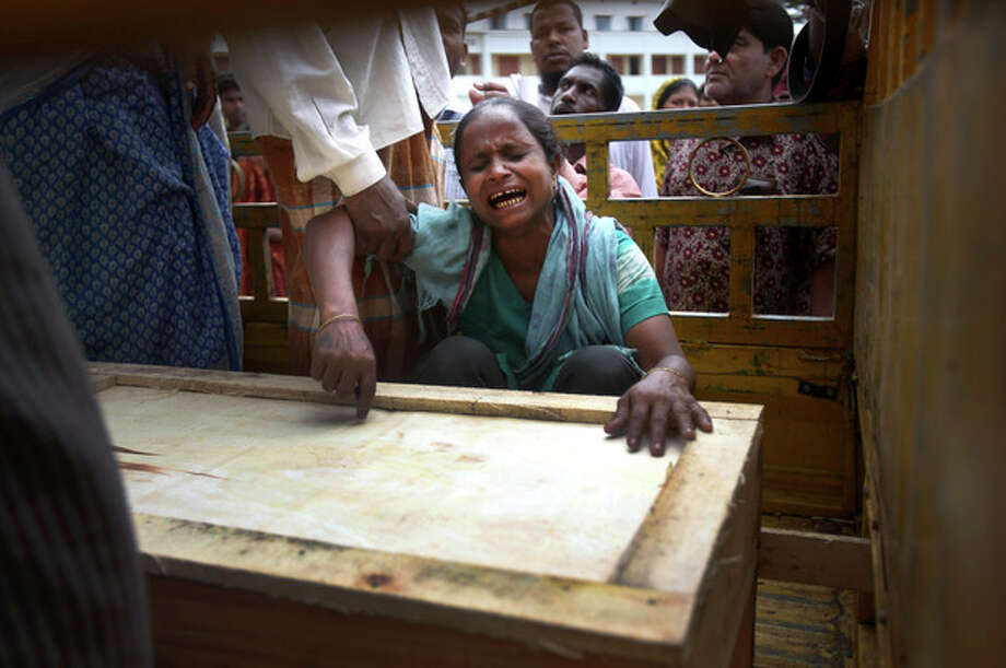 "A woman cries over a coffin containing the body of her relative who was retrieved from the rubble after a garment factory building collapsed last week and brought to the morgue for identification, Saturday, May 4, 2013 in Savar, near Dhaka, Bangladesh. The death toll in the accident rose to more than 530 on Saturday, a day after the country's finance minister downplayed the impact of the disaster on the garment industry, saying he didn't think it was ""really serious."" (AP Photo/Wong Maye-E) / AP"