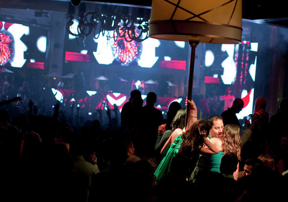 With a private table spotlighted, right, revelers dance to the music played by DJ Afrojack inside the XS nightclub in Las Vegas on Sunday, Jan. 20, 2013. (AP Photo/Julie Jacobson) / AP