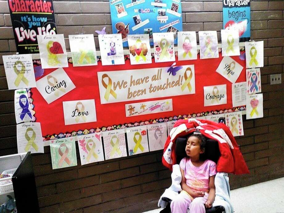 Contributed photoIsabella sits in front of a wall of golden ribbons at Marvin Elementary.