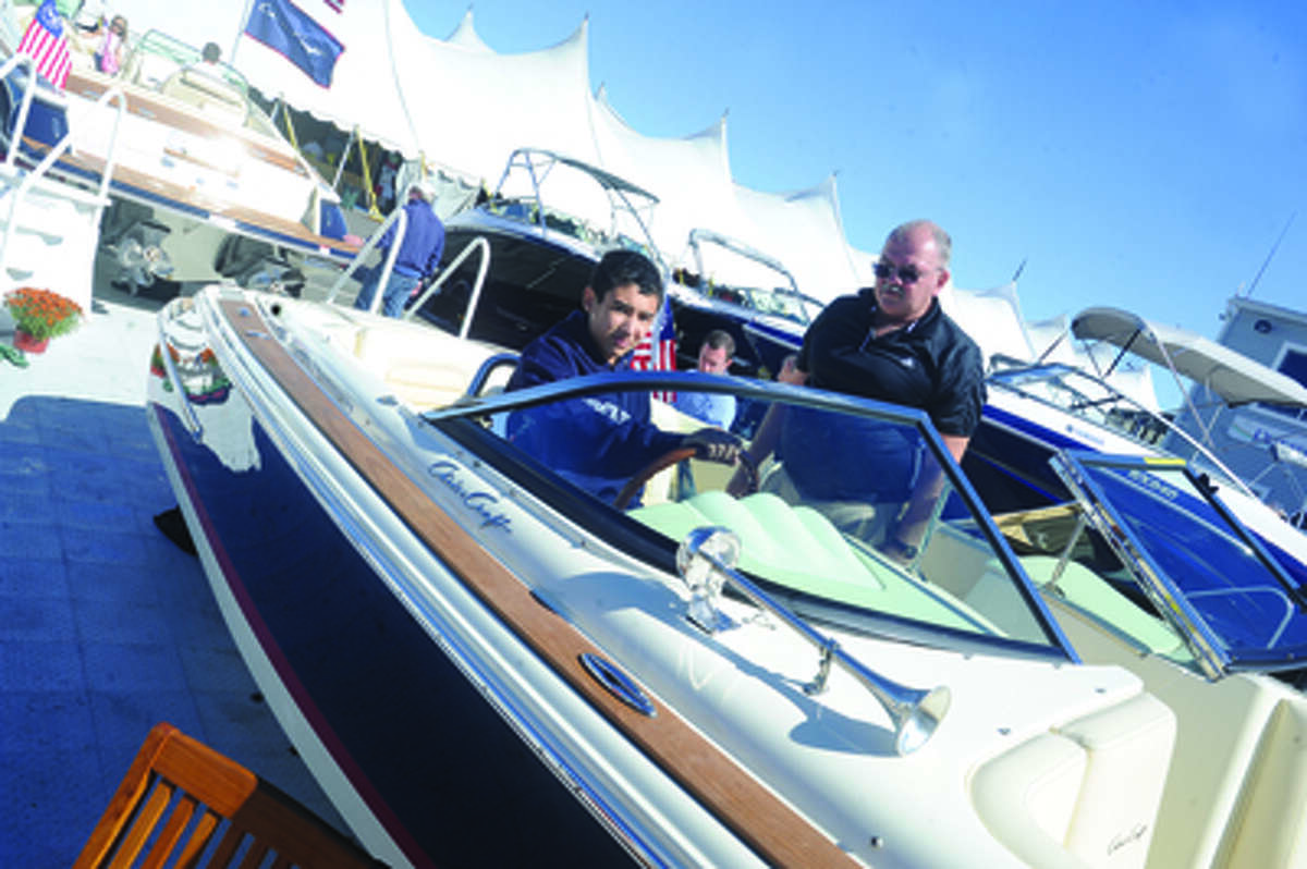 Jimmy Wunderlich and his son Eric 13 aboard a Chris Craft boat Sunday at the boat show in Norwalk. hour photo/Matthew Vinci