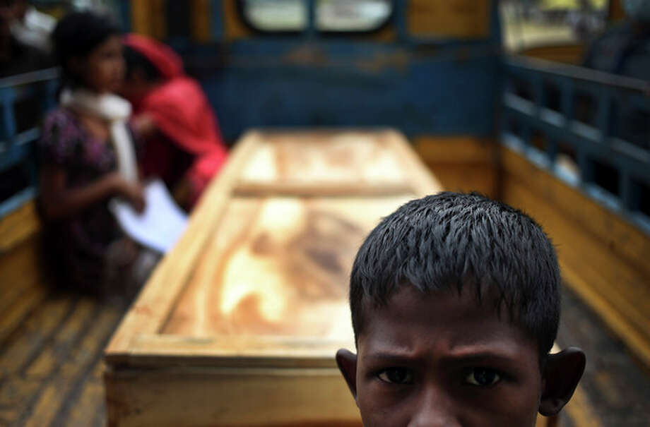 A boy waits in front of a pickup truck that is transporting the body of a victim from the rubble of the garment factory collapse, Sunday, May 5, 2013 in Savar, near Dhaka, Bangladesh. The death toll from the collapse of a shoddily built garment-factory building in Bangladesh continued its horrifying climb, reaching 580 on Sunday with little sign of what the final number will be. The disaster is likely the worst garment-factory accident ever, and there have been few industrial accidents of any kind with a higher death toll.(AP Photo/Wong Maye-E) / AP