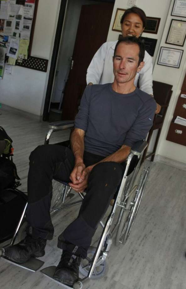 French national Armand Manel, 42, one of the survivors of an avalanche at Mount Manaslu in northern Nepal, is carried on a wheelchair at a clinic in Katmandu, Nepal, Sunday, Sept. 23, 2012. The avalanche swept away climbers on a Himalayan peak in Nepal on Sunday, leaving at least nine dead and six others missing, officials said. (AP Photo/Binod Joshi)
