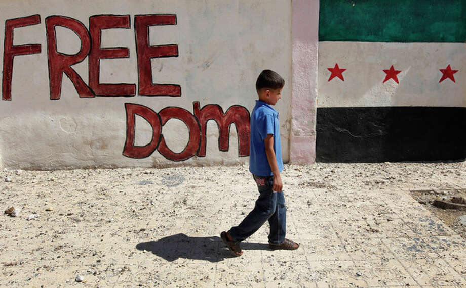 A Syrian boy walks in front of wall painted with colors of the Syrian revolutionary flag, right, in Marea village, on the outskirts of Aleppo, Syria, Sunday Sept. 23, 2012. Syria's bloody 18-month conflict, which activists say has killed nearly 30,000 people, has so far eluded all attempts at international mediation. (AP Photo/Hussein Malla) / AP