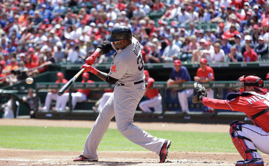 Boston Red Sox designated hitter David Ortiz (34) hits a two run homer in front of Texas Rangers catcher A.J. Pierzynski (12) during the first inning of an MLB American League baseball game Sunday, May 5, 2013, in Arlington, Texas. (AP Photo/LM Otero) / AP