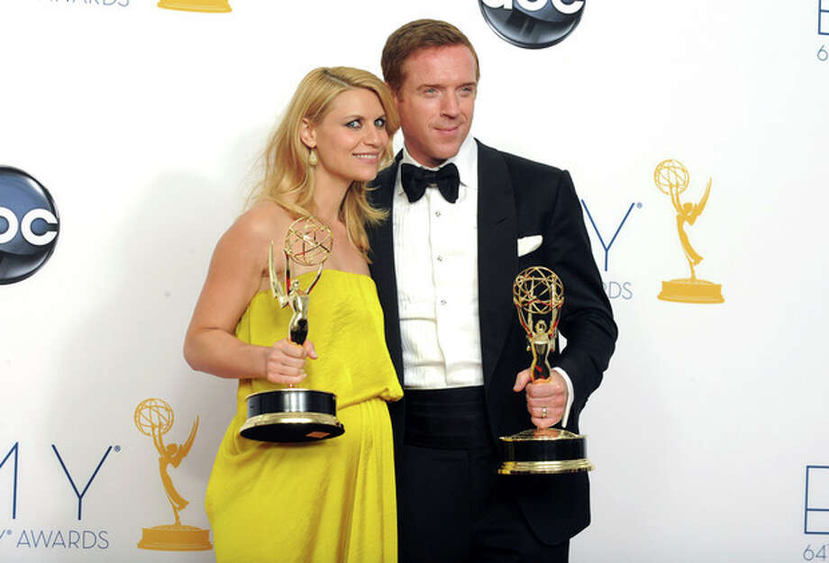 "Actress Claire Danes, winner of the Emmy for outstanding lead actress in a drama series for ""Homeland,"" left, and actor Damien Lewis, winner of the Emmy for outstanding lead actor in a drama series for ""Homeland"" pose together backstage at the 64th Primetime Emmy Awards at the Nokia Theatre on Sunday, Sept. 23, 2012, in Los Angeles. (Photo by Jordan Strauss/Invision/AP) / Invision"