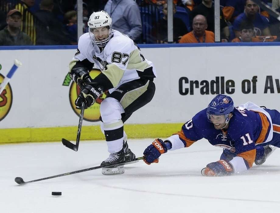 Pittsburgh Penguins' Sidney Crosby, left, passes past New York Islanders' Lubomir Visnovsky during the first period of Game 3 of an NHL hockey Stanley Cup first-round playoff series, Sunday, May 5, 2013, in Uniondale, N.Y. (AP Photo/Seth Wenig) / AP