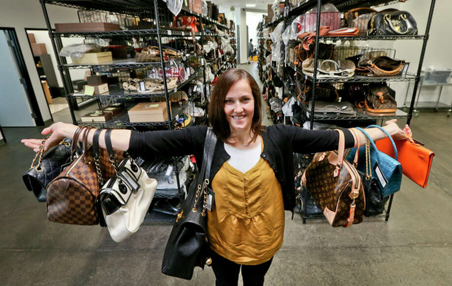 This photo taken May 2, 2013, shows Sarah Davis, co-owner of Fashionphile.com, posing with her bags in a company warehouse in the Carlsbad, Calif. The Internet company sells rare, vintage, and discontinued previous owned bags and is facing the complicated task of dealing with new state regulations on Internet sale taxes. (AP photo/Lenny Ignelzi) / AP