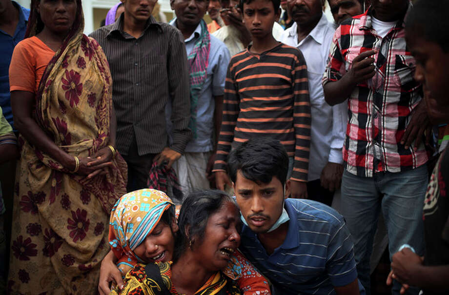 A woman is comforted as she grieves after identifying the body of her daughter, a victim of the garment factory collapse, Sunday, May 5, 2013 in Savar, near Dhaka, Bangladesh. The death toll from the collapse of a shoddily built garment-factory building in Bangladesh continued its horrifying climb, reaching 580 on Sunday with little sign of what the final number will be. The disaster is likely the worst garment-factory accident ever, and there have been few industrial accidents of any kind with a higher death toll.(AP Photo/Wong Maye-E) / AP