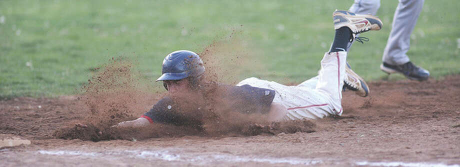 Hour photo/John NashBrien McMahon's Mark Ballard dives back to first base and gets a face full of dirt after being tagged out during a rundown between first and second during Monday's game against Darien in Norwalk. The visiting Blue Wave claimed a 7-2 victory.