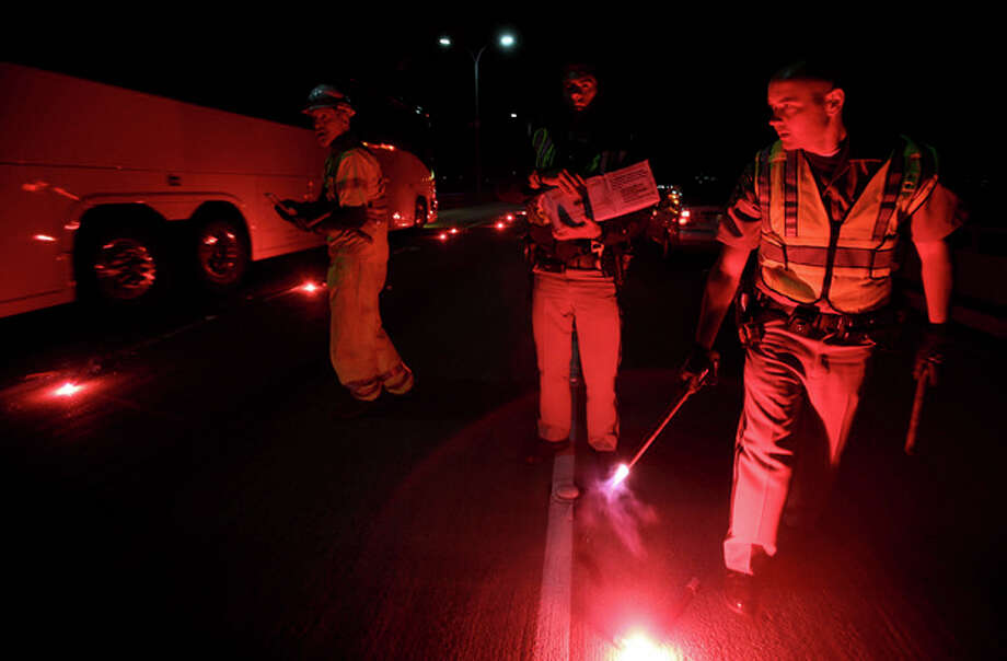 California Highway Patrolmen light flares as they investigate the scene of a limousine fire on the westbound side of the San Mateo-Hayward Bridge in Foster City, Calif., on Saturday, May 4, 2013. Five people died when they were trapped in the limo that caught fire as they were traveling, and four others and the driver were able to escape, according to the Oakland Tribune-Bay Area News Group. (AP Photo/Oakland Tribune-Bay Area News Group, Jane Tyska) / Oakland Tribune-Bay Area News Group