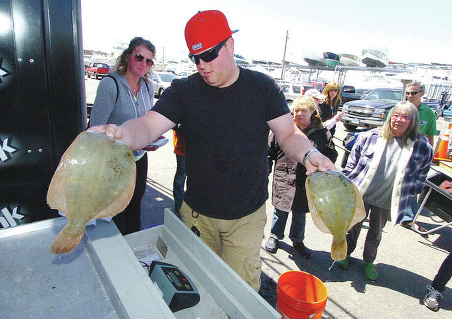 Hour Photo/Alex von Kleydorff Michael Staff weighs some of the flounders at South Norwalk Boat Club's 50th anniversary Auxiliary Flounder Tournament at South Norwalk Boat Club. / 2013 The Hour Newspapers