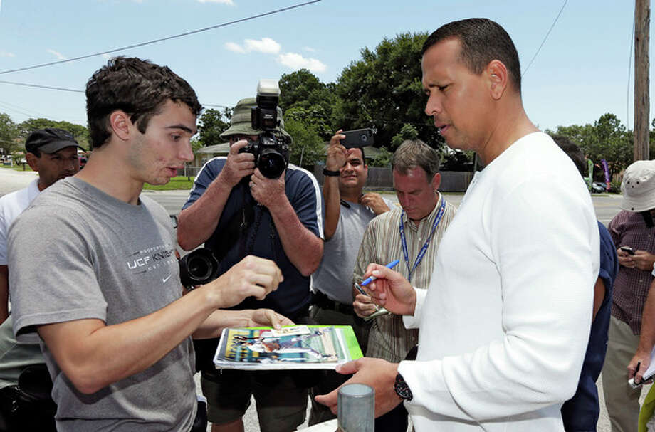 New York Yankees third baseman Alex Rodriguez, right, signs autographs for fans after reporting to the Yankees' Minor League complex for rehabilitation Monday, May 6, 2013, in Tampa, Fla. Rodriguez is getting back on the field for the first time since surgery on his left hip almost four months ago. (AP Photo/Chris O'Meara) / AP