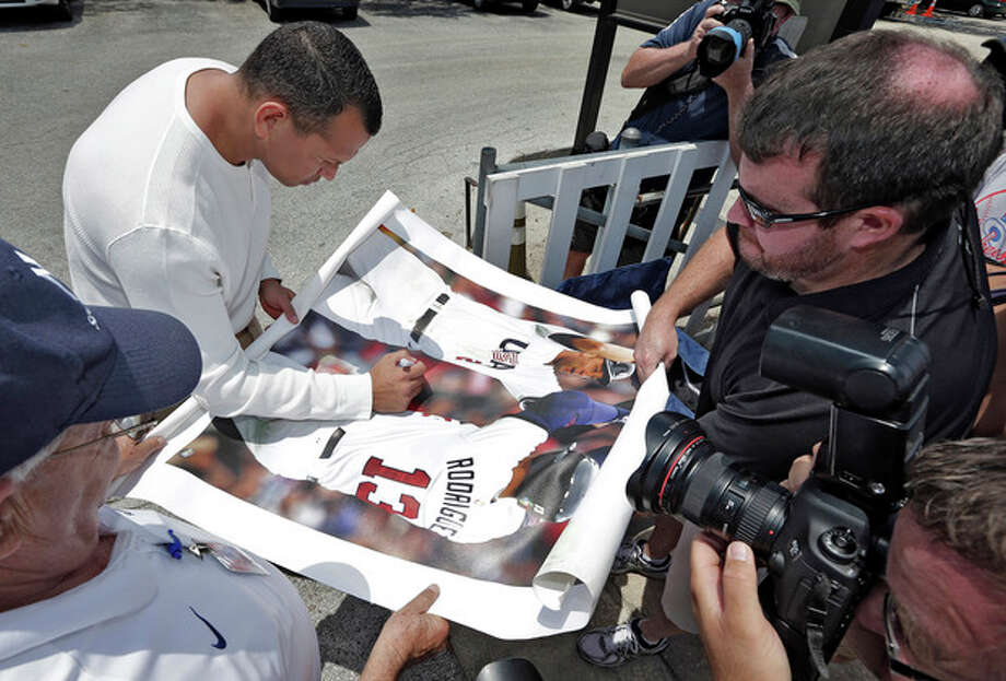 New York Yankees third baseman Alex Rodriguez, upper left, signs autographs for fans after reporting to the Yankees' Minor League complex for rehabilitation Monday, May 6, 2013, in Tampa, Fla. Rodriguez is rehabbing from hip surgery. (AP Photo/Chris O'Meara) / AP
