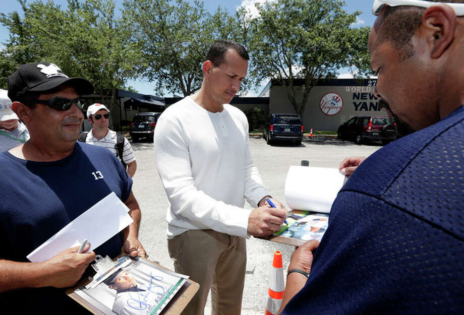 New York Yankees third baseman Alex Rodriguez, center, signs autographs for fans after reporting to the Yankees' Minor League complex for rehabilitation Monday, May 6, 2013, in Tampa, Fla. Rodriguez is rehabbing from hip surgery. (AP Photo/Chris O'Meara) / AP