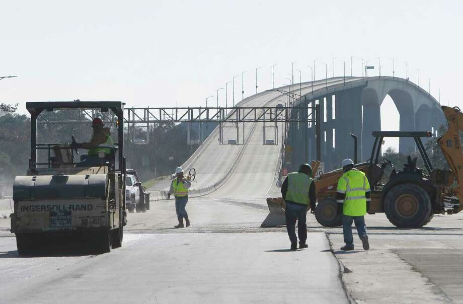 Workers are shown along the Harris County Toll Road Authority Sam Houston Tollway Ship Channel Bridge Sunday, Jan. 10, 2016, in Houston. The bridge was closed on Friday, Jan. 8 for a conversion to all-electronic tolling. The bridge is scheduled to reopen by 5 a.m. Monday, January 11. ( Melissa Phillip / Houston Chronicle ) Photo: Melissa Phillip, Staff / © 2016 Houston Chronicle