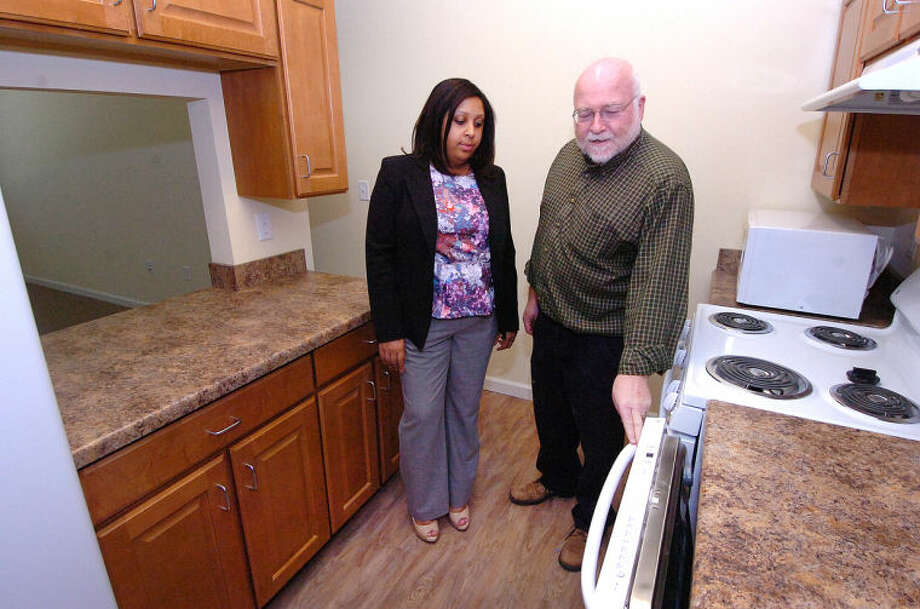 Hour Photo/Alex von Kleydorff . Director of Housing Development Keith Cryan and Property Manager Johneisha DuBose walk through the kitchen in a one bedroom unit at Wilton Commons