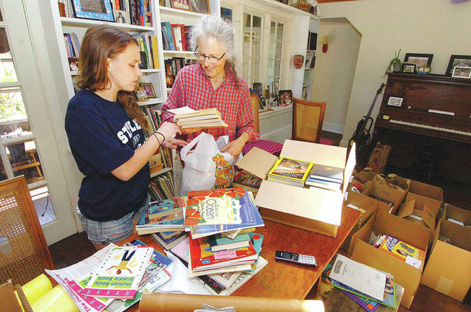 Hour Photo/Alex von Kleydorff Sherrie Jagerson and Granddaughter Adelaide Fowle sort through books that will add up to 1,400 they have so far in their database. They need 3000 for their United with Kenya book campaign / 2013 The Hour Newspapers