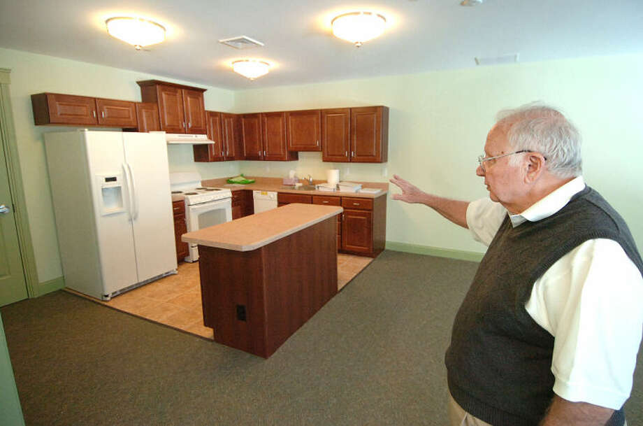 Hour Photo/Alex von Kleydorff Wilton Commons Board Member Ken Dartley shows the full kitchen off the commons room at Wilton Commons