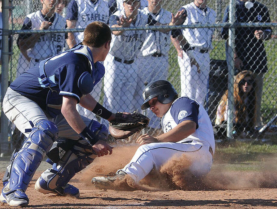 Hour photo/Matthew VinciBryan Terzian of Staples slides safely across the plate as Wilton catcher Alex Jacobson, left, turns too late to apply a tag. Terzian and the Wreckers went on to claim a 5-3 victory over the visiting Warriors in Monday's game in Westport.