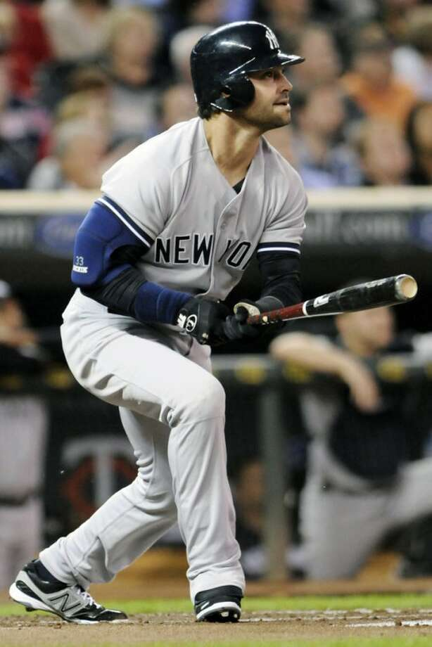 New York Yankees' Nick Swisher watches his two-run home run off Minnesota Twins pitcher Liam Hendriks in the first inning of a baseball game, Monday, Sept. 24, 2012, in Minneapolis. (AP Photo/Jim Mone)