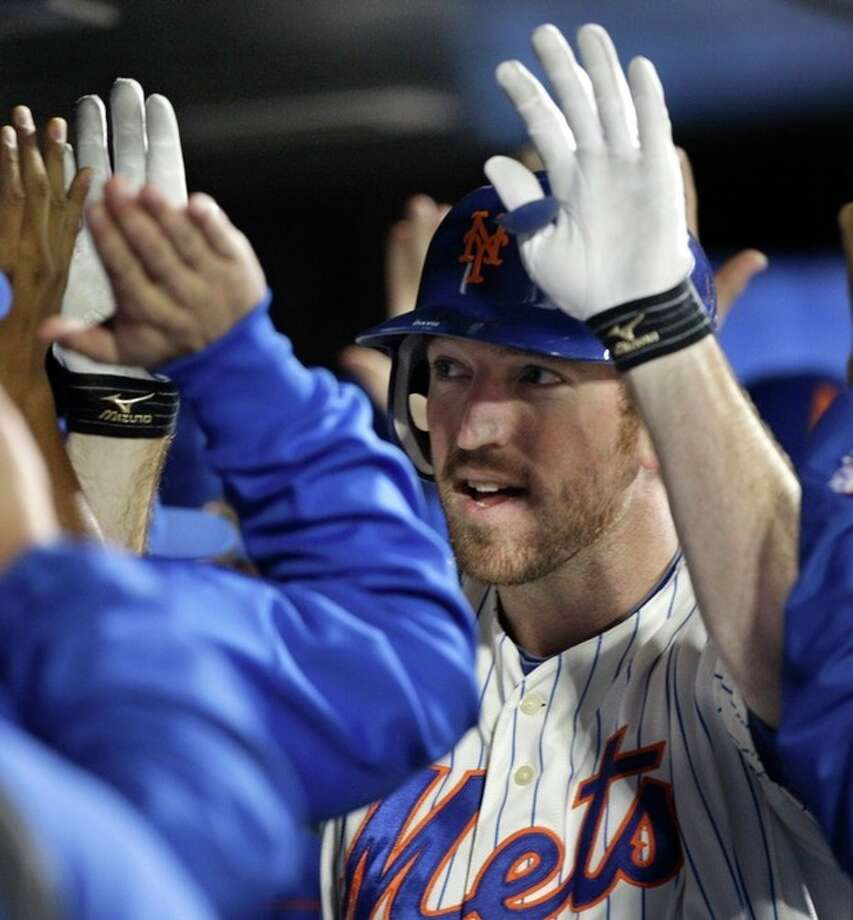 New York Mets' Ike Davis, center, is congratulated by teammates in the dugout after his three-run home run off Pittsburgh Pirates reliever Jeff Karstens in the fifth inning of a baseball game in New York, Monday, Sept. 24, 2012. (AP Photo/Kathy Willens) / AP
