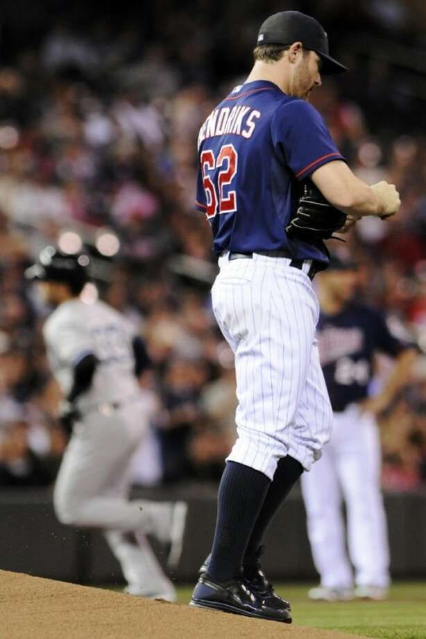 Minnesota Twins pitcher Liam Hendriks looks away after giving up a two-run home run to New York Yankees' Nick Swisher, left, in the first inning of a baseball game, Monday, Sept. 24, 2012, in Minneapolis. (AP Photo/Jim Mone)