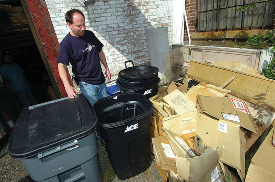 Norwalk Luggage manager Adam Bosworth moves a trash bin at the rear of his Wall Street Store. / 2012 The Hour Newspapers