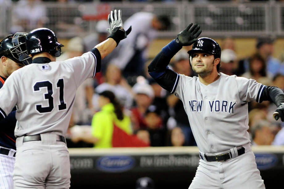New York Yankees' Ichiro Suzuki, left, of Japan, congratulates Nick Swisher after Swisher's two-run home run off Minnesota Twins pitcher Liam Hendriks in the first inning of a baseball game, Monday, Sept. 24, 2012, in Minneapolis. (AP Photo/Jim Mone) / AP