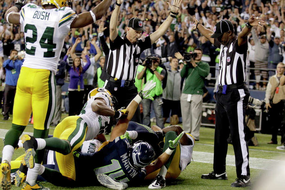 Officials signal a touchdown by Seattle Seahawks wide receiver Golden Tate, obscured, on the last play of an NFL football game against the Green Bay Packers, Monday, Sept. 24, 2012, in Seattle. The Seahawks won 14-12. (AP Photo/Stephen Brashear) / FR159797 AP