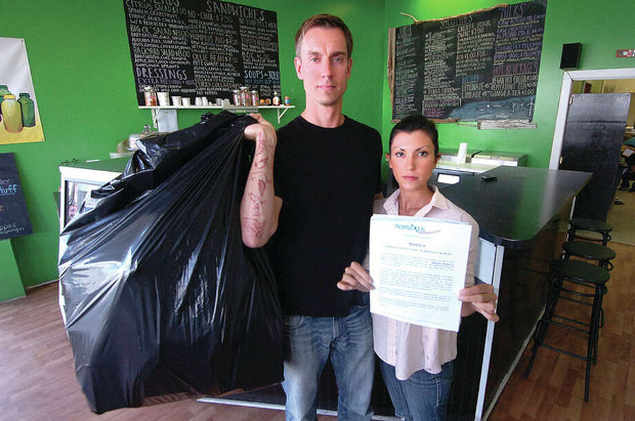 Hour photos / Alex von KleydorffMichael Hvizdo holds trash while his wife, Carissa, holds a notice at their business, The Stand Juice Co., on Wall Street in Norwalk. The notice from the city of Norwalk describes a Garbage Collection Schedule change. / 2012 The Hour Newspapers