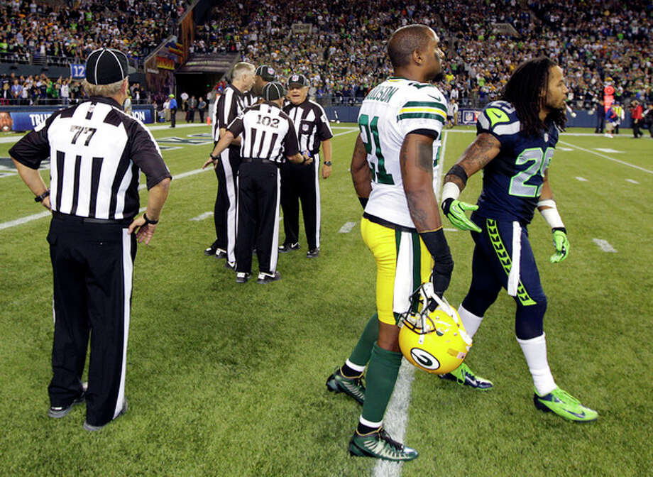 Officials discuss the final play of the game as Green Bay Packers' Charles Woodson, second from right, and Seattle Seahawks' Earl Thomas, right, leave the field in the second half of an NFL football game, Monday, Sept. 24, 2012, in Seattle. The final play was ruled a Seattle touchdown as the Seahawks defeated the Packers 14-12. (AP Photo/Ted S. Warren) / AP