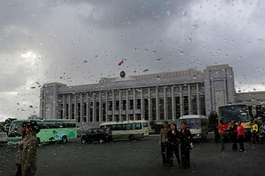 In this Sept. 19, 2012 photo, North Koreans walk in front of the Mansudae Assembly Hall in Pyongyang, North Korea. North Korea's rubber-stamp parliament is convening a new session that is drawing attention because it is the second in less than six months. The 687-member Supreme People's Assembly gathers Tuesday, Sept. 25, 2012 in the North Korean capital. (AP Photo/Vincent Yu) / AP