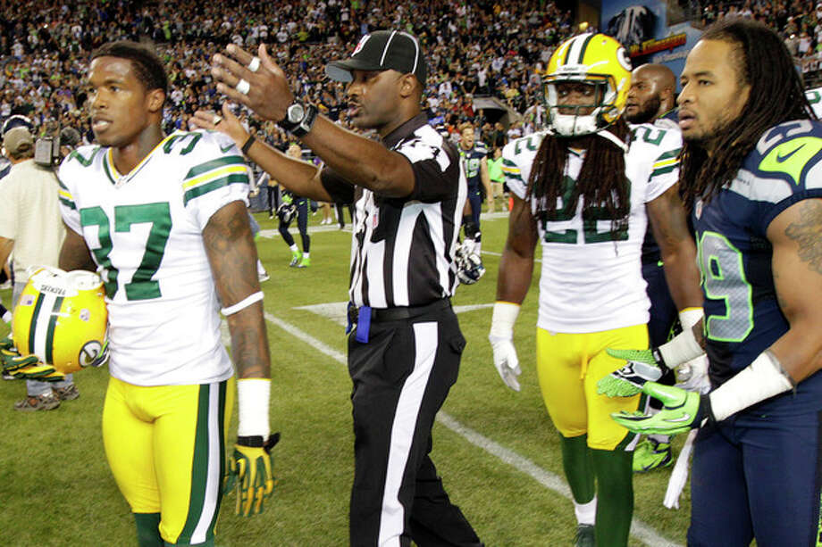 An official gestures as Green Bay Packers cornerback Sam Shields (37), safety Jerron McMillian (22) and Seattle Seahawks free safety Earl Thomas (29) leave the field in the second half of an NFL football game, Monday, Sept. 24, 2012, in Seattle. After a period of confusion, a Seahawks touchdown by wide receiver Golden Tate was allowed to stand for the 14-12 win. (AP Photo/Ted S. Warren) / AP